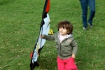 Adorable child walking around with a penguin kite. What else is there in life?